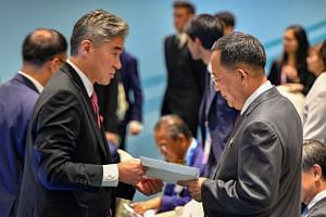 North Korea's Foreign Minister Ri Yong Ho is handed US President Donald Trump's reply to North Korean leader Kim Jong Un's letter, by a member of the US delegation at the Asean meeting in Singapore on Aug 4, 2018.