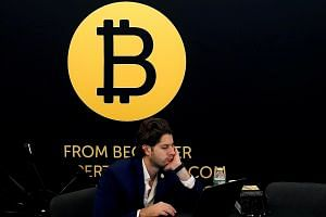 """Bitcoin - with its logo seen here at the Consensus 2018 blockchain technology conference in New York City in May - is not discovered or created by """"miners"""". Rather, they get new coins as a reward for securing the network."""