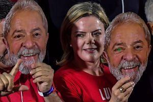 Workers' Party president Gleisi Hoffmann holding a mask depicting Brazil's former president Luiz Inacio Lula da Silva.