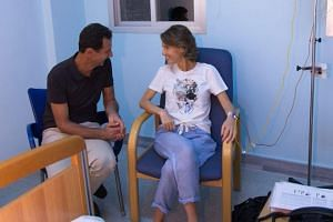 Bashar al-Assad sits next to his wife, Asma, as she receives treatment for breast cancer.