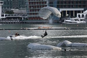 Naval Combat Divers from the Republic of Singapore Navy's Naval Diving Unit performing a freefall water jump next to the Marina Bay Floating Platform, on June 30, 2018.
