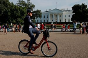 A man bicycles past the White House in Washington.