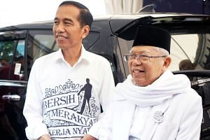 Indonesia's President Joko Widodo (left) with vice-presidential candidate Ma'ruf Amin after submitting their nomination papers to the General Election Commission in Jakarta on Aug 10, 2018.