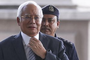 Former Malaysia prime minister Najib Razak is escorted by Royal Malaysian Police as he arrives at the Kuala Lumpur High Court, Malaysia, on Aug 10, 2018.