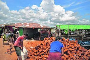 Rohingya men fill bags with bricks at the Kutupalong camp near Cox's Bazar in Bangladesh on July 18, 2018.