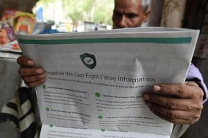 A man reads a newspaper with a full back page advertisement from WhatsApp intended to counter fake information, in New Delhi, on July 10, 2018.