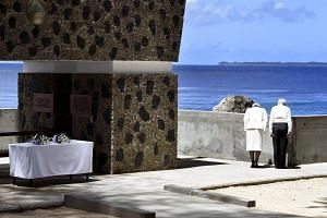 Japan's Emperor Akihito (right) and Empress Michiko bow towards Angaur Island after they offered flowers to the cenotaph for the war dead in the western Pacific area, on Palau's Peleliu Island.