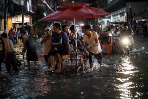 A rickshaw carrying passengers on a flooded street in Manila, on Aug 11, 2018.