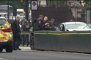 Forensics officers examining evidence around the silver Ford Fiesta that was driven into a barrier at the Houses of Parliament yesterday. Three people were injured in the attack. TV footage showing the arrest of a handcuffed driver in his late 20s ou