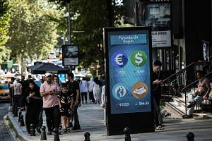 A digital billboard giving updates on currencies and the Turkish stock exchange in Istanbul on Monday. Last Friday, the lira depreciated by 14 per cent.