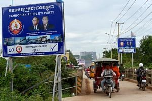 Commuters pass the billboard of the ruling Cambodian People's Party bearing the portraits of Cambodia's strongman Premier Hun Sen (right) and National Assembly President Heng Samrin in Kandal province on Aug 15, 2018.