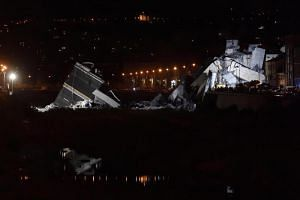 Rescuers work into the night at the site of the Morandi viaduct, upon which the A10 motorway runs, that collapsed in Genoa, Italy, on Aug 14, 2018.