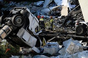 Rescuers inspecting the rubble and wreckages by the Morandi motorway bridge after a section collapsed earlier in Genoa, on Aug 14, 2018.