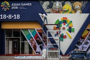 A worker paints an installation showing mascots Kaka (left), Bhin Bhin (centre), and Atung ahead of the 2018 Asian Games in Jakarta, on Aug 14, 2018.  The peak of the dry season is expected to occur during the Games.