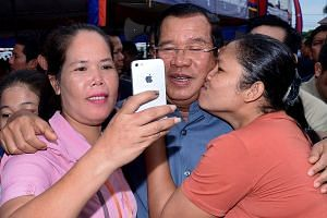 Cambodian Prime Minister Hun Sen (centre) posing with garment workers during a visit to a factory in Phnom Penh yesterday. In a statement, the National Election Committee confirmed yesterday that his Cambodian People's Party had won all 125 parliamen