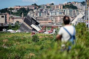 A resident views the Morandi motorway bridge after it partially collapsed in Genoa, Italy, on Aug 15, 2018.