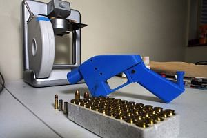 A Liberator pistol next to the 3D printer on which its components were made in Hanover, Maryland, on July 17, 2013.