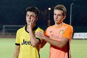 Balestier Khalsa's Sanjin Vrebac (far left, with Hougang United's Antoine Viterale) looking stunned while having a hand on his cheek at Hougang Stadium on Wednesday. The Austrian midfielder has alleged he was slapped by Hougang's general manager Matt
