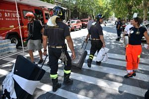 Firefighters accompany residents to get their belongings from their homes, in Genoa, Italy, on Aug 16, 2018.