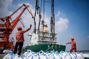 Workers unloading bags of chemicals at a port in Zhangjiagang in China's eastern Jiangsu province, on Aug 7, 2018.