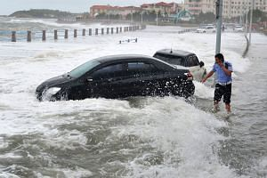 A police officer making a phone call on a flooded street in Qingdao as waves caused by typhoon Yagi surge past a barrier along the seacoast on Aug 13, 2018. Summer is China's typhoon season.