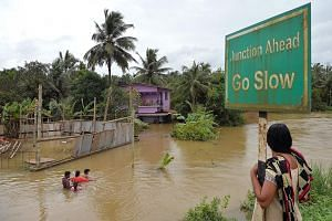 Residents wading through a flooded street next to marooned houses on the outskirts of Kerala's northern Kozhikode district. With thousands still trapped in flooded areas, power and communication lines down and fresh alerts of further torrential rain,