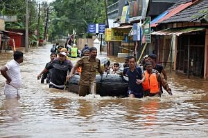 Rescuers evacuating people from a flooded area in Aluva, Kerala, yesterday. Some of the victims have reached out to their families and friends in Singapore for help. Mr Rajesh Chandran (far left)with his family at the family home in Kerala last year.