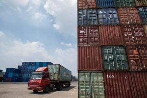 A file picture taken on Aug 7, 2018, shows a truck transporting a container at a port in Zhangjiagang, China.