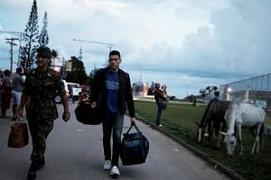 A Venezuelan man (right) is helped by Brazilian Colonel Zannata across the border after he shows his onwards airline ticket for Foz do Iguacu at the Pacaraima border control, Roraima state, Brazil, on Aug 19, 2018.