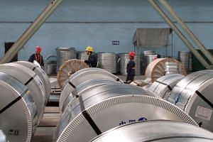 Workers pack cold rolled steel coil at a steel company in Zhangjiagang, Jiangsu province, China, on April 27, 2018.