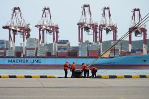Workers help to dock a cargo ship at a port in Qingdao, Shandong province, China.