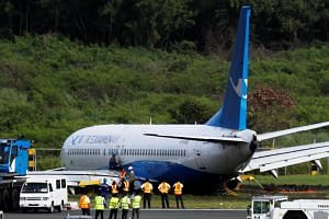 Workers try to remove a Xiamen Air Boeing 737-800 from the tarmac after it skidded off at the runway of Ninoy Aquino International airport in Paranaque, Metro Manila, in the Philippines, on Aug 17, 2018.