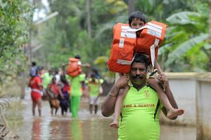 Kerala and Tamil Nadu Fire Force personnel carrying children on their shoulders through flood waters during a rescue operation in Annamanada village in Thrissur District, Kerala, on Sunday. Rescuers waded into submerged villages in a desperate search