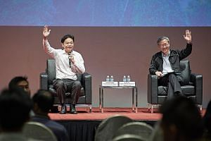 Minister for National Development Lawrence Wong (far left) and Reach chairman Sam Tan getting the audience at yesterday's forum about the National Day Rally to raise their hands if they are among the Merdeka Generation.