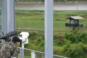 A South Korean soldier looks through binoculars on a viewing deck of Imjingak peace park near the Demilitarised Zone in the border city of Paju on June 11, 2018.