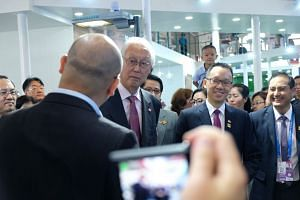 Emeritus Senior Minister Goh (centre) and Senior Parliamentary Secretary for Trade and Industry Tan Wu Meng (second from right) touring the Singapore pavilion at the Smart China Expo in Chongqing, China, on Aug 23, 2018.