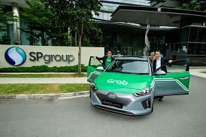 Mr Goh Chee Kiong (right), SP Group's strategic development head poses with Mr Lim Kell Jay, head of Grab Singapore.