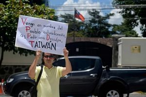 """A man in front of the Taiwanese embassy in San Salvador on Tuesday holding a placard that reads """"Taiwan, in the name of the Salvadoran people, I come to ask for forgiveness"""". El Salvador is the fifth country in the last two years to switch allegi"""
