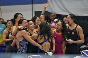 Left: Roanne Ho benefited after a fellow swimmer was disqualified, leaving her second in the 50m breaststroke at the Gelora Bung Karno Aquatic Centre in Jakarta. Below: The 4x100m medley relay teams from Hong Kong and Singapore embrace one another af