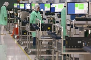 Employees of semiconductor giant, Infineon, working on the plant-floor in its facilities at Kallang Way. Factory output has cooled since hitting growth of 10.9 per cent and 13.0 per cent in April and May this year.