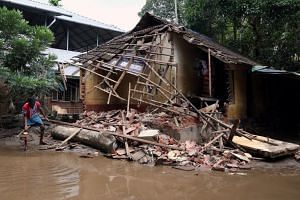 A man removes debris from a collapsed house after floods in Paravur, in the southern state of Kerala, India, on Aug 23, 2018.