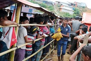 Rohingya refugees collecting food from a relief distribution centre in the Balukhali camp in Bangladesh's Cox's Bazar district. There are still almost one million refugees living in basic shelters in an area that suffers some of the worst monsoon con
