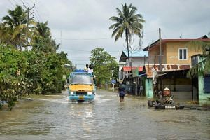 A mini-truck makes its way down a flooded road in Paravur on the outskirts of Kochi in the south Indian state of Kerala, on Aug 20, 2018.