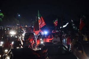 Supporters of Pakistan's cricketer-turned politician Imran Khan, head of the Pakistan Tehreek-e-Insaf (Movement for Justice) party, cheer as they celebrate in Lahore, on July 26, 2018.