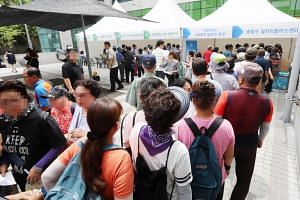 Jobseekers wait in a long line to enter a job fair at a ward office in Seoul, South Korea, on Aug 20 2018, amid the country's worst-ever unemployment crisis.