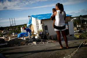 Samuel Vasquez rebuilds his partially destroyed house, as wife Ysamar Figueroa looks on with son Saniel.