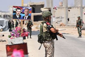 Russian and Syrian forces stand guard at a crossing in Syria, near posters of Syrian President Bashar al-Assad and Russian counterpart Vladimir Putin.