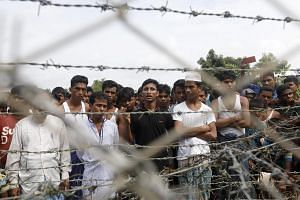 Rohingya refugees gather near a fence between the Bangladesh-Myanmar border in Maungdaw district, Rakhine State, on Aug 24, 2018.