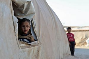A young boy peeks out of a tent in a camp for the displaced from Syrian provinces on Aug 26, 2018.
