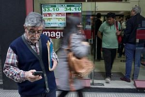 Currency exchange values are displayed in the buy-sell board of a bureau de exchange in Buenos Aires, on Aug 29, 2018.